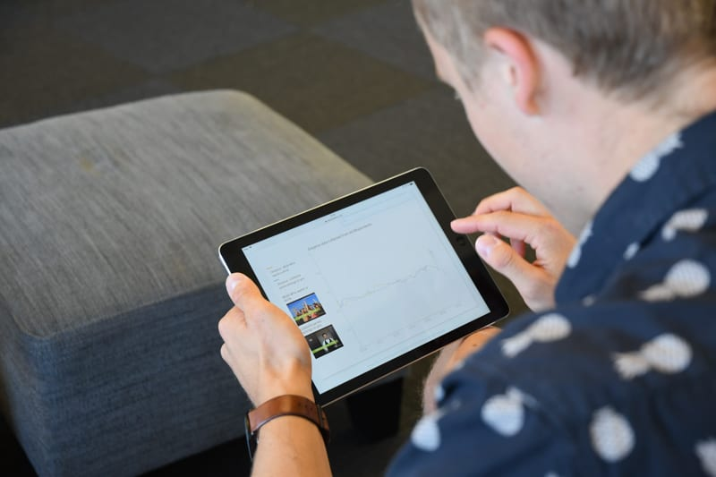man holding a tablet and looking at the screen