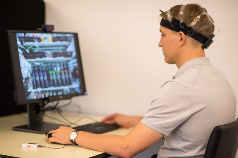 EEG Eye Tracking Facial Expression Analysis man with eeg headset in front of a computer screen