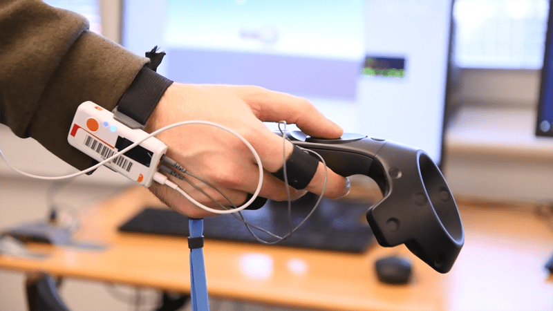 hand with biometric sensors holding a virtual reality remote controller