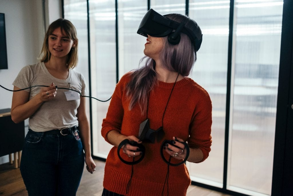 woman wearing a virtual reality head set and holding remote controllers
