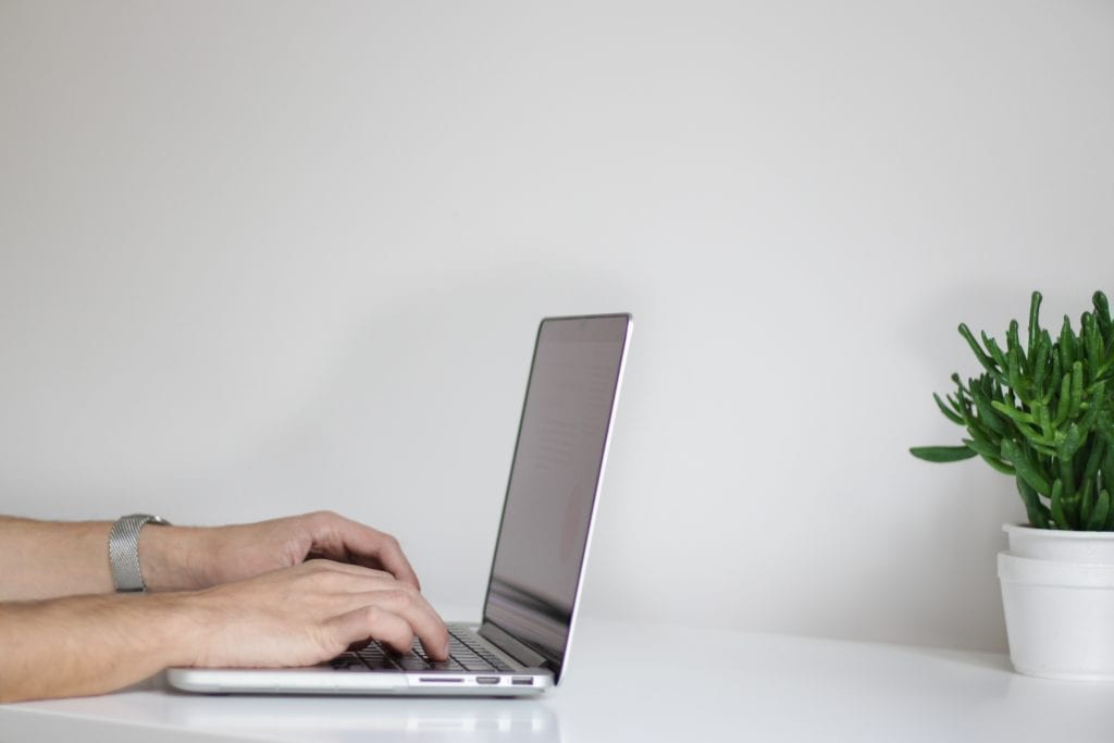 man's hands typing on a laptop sitting down at a table with a plant on top