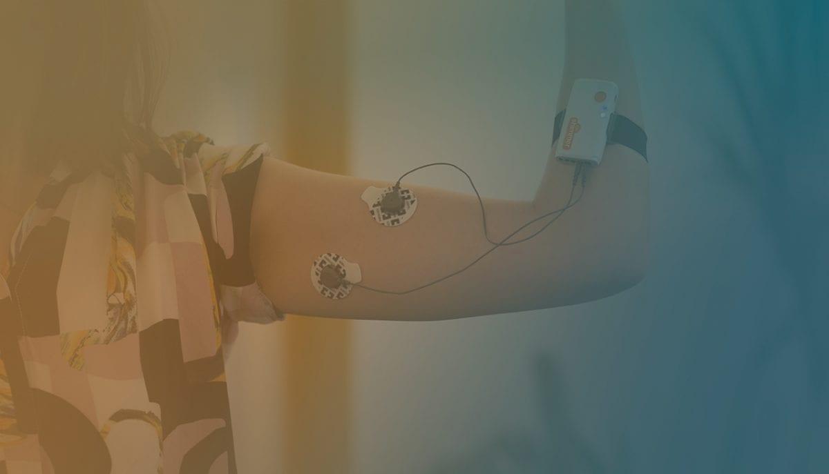Girl flexing her arm wearing EMG