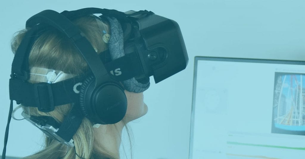 woman wearing VR headset next to a computer