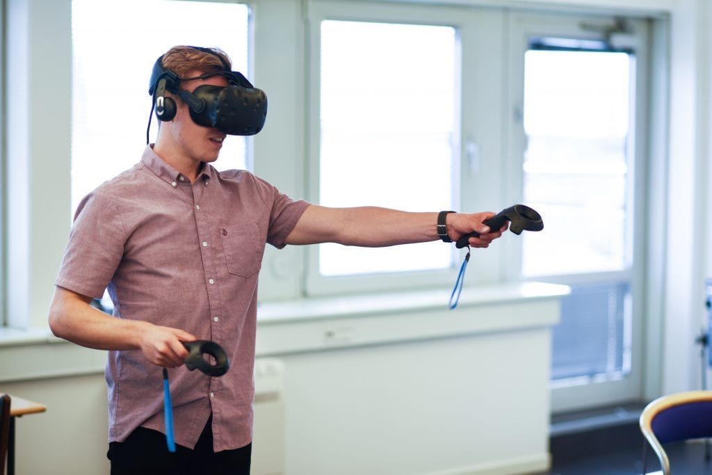 Man wearing VR headset with joystick in extended arm