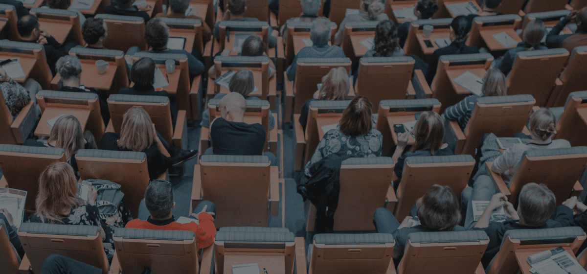 conference attendees sitting in seats in a theater