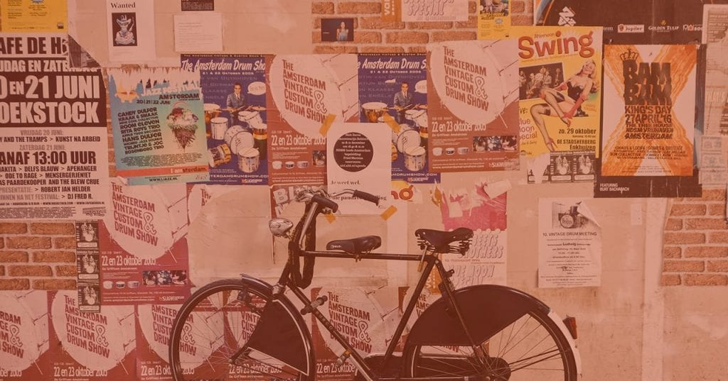 Bike in front of bulletin board with posters