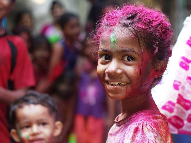 closeup of a smiling little girl with paint on her hair, face, and clothes