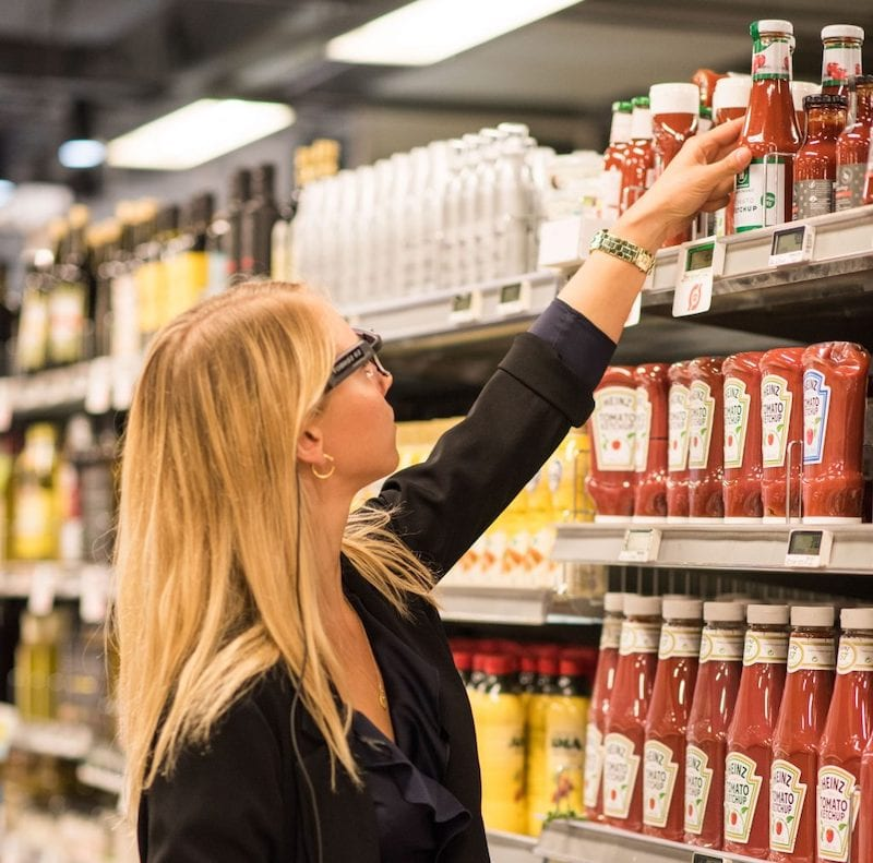 woman wearing eye tracking glasses while reaching for ketchup at a supermarket