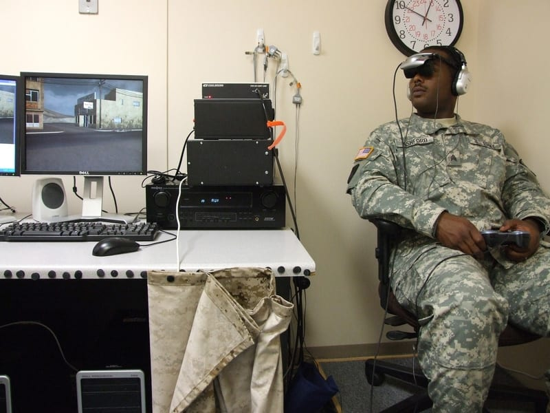 soldier sitting on a chair in a testing room wearing virtual reality headset next to a screen and tech equipment