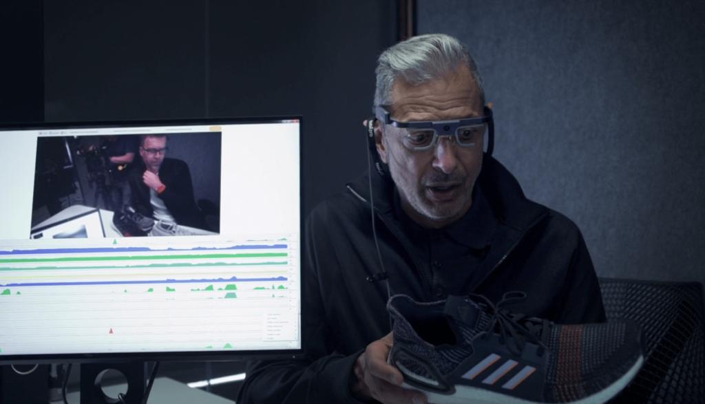 Jeff Goldblum wearing eye tracking glasses looking at a sneaker